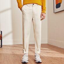 Hose mit schraegen Taschen, seitlichen Knopfen und Riemen am Saum
