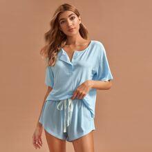 Schlafanzug Set mit sehr tief angesetzter Schulterpartie und Knopfen vorn