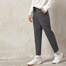 Pantalones unicolor con bolsillo oblicuo de cintura con cordon