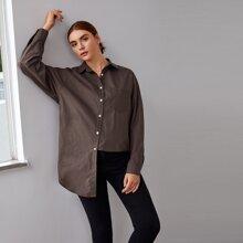 Bluse mit sehr tief angesetzter Schulterpartie, gebogenem Saum und Taschen Flicken
