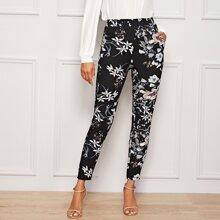Hose mit botanischem Muster und schraegen Taschen