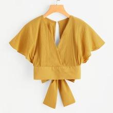 Blusa corta cruzada con abertura y lazo en la espalda