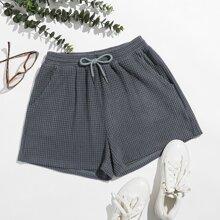 Shorts mit Kordelzug um die Taille und schraegen Taschen