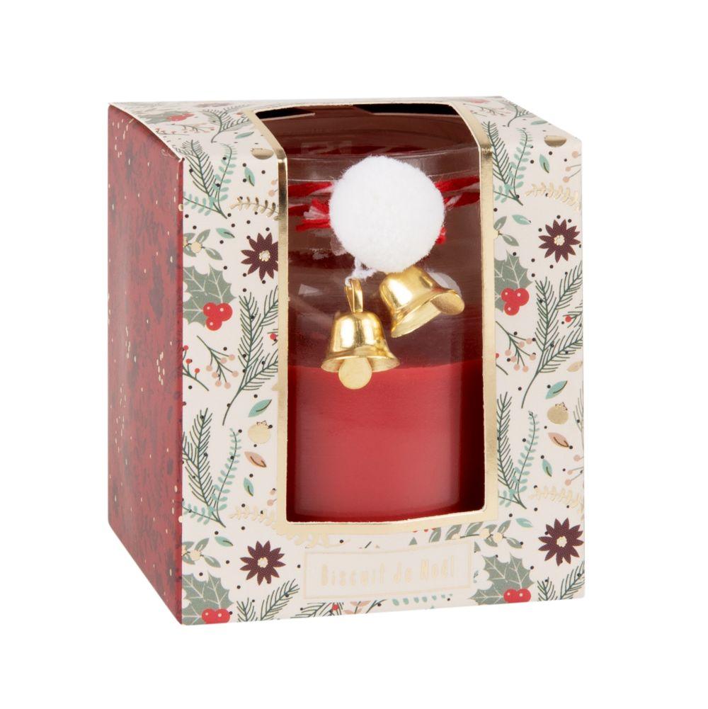 Duftkerze im roten Glasgefaess und elfenbeinfarbene Pompons