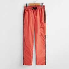 Pantalones viento de lado de rayas con bolsillo con solapa