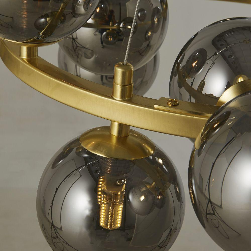 Haengelampe mit 15 Kugelschirmen aus schwarz getontem Glas, Gestell aus goldfarbenem Metall